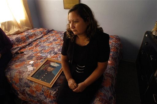 This Nov. 19, 2004, file photo shows Rosa Maria Peralta sitting on her son's bed in his bedroom reflects back on her memories with her son, Marine Sgt. Rafael Peralta in San Diego, Calif. The Navy will posthumously award a Navy Cross to Peralta, who was k