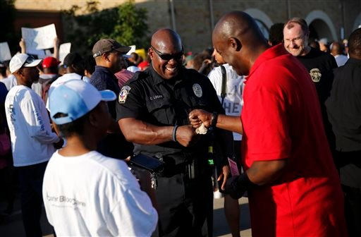 McKinney police officer Curtis Logan, center, receives a fist bump from Mark Matthews of North Dallas as the two attended the protest that started at Joyce Kelley Comstock Elementary, Monday June 8, 2015. The group marched to the Craig Ranch pool where Mc
