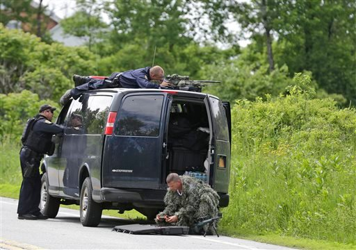 A law enforcement agent looks through a sniper scope while another in camouflage assembles a weapon during a search for two escaped killers in Boquet, N.Y., Tuesday, June 9, 2015.