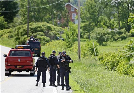 Heavily armed law enforcement agents patrol the edge of road during a search for two escaped killers near Boquet, N.Y., Tuesday, June 9, 2015.