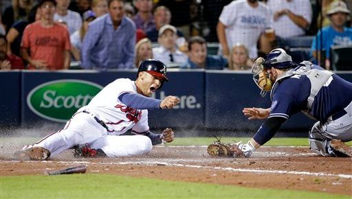 Atlanta Braves' Andrelton Simmons, left, beats the tag by San Diego Padres catcher Derek Norris to score off a single by teammate Jonny Gomes in the sixth inning of a baseball game Tuesday, June 9, 2015, in Atlanta. (AP Photo/David Goldman)