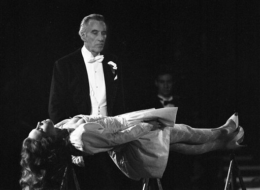 """In this file photo dated December 5, 1987, the lights were turned down low as British actor Christopher Lee performs as magician in the act """"The Floating Virgin""""."""