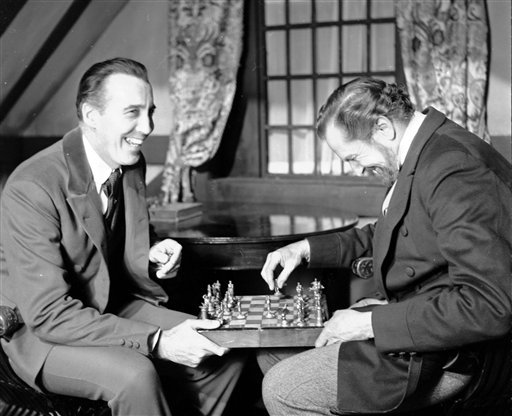 """In this file photo dated Dec. 17,1968, British actor Christopher Lee, left and American actor Vincent Price, share a joke whilst playing chess during a break in the filming of Edgar Allen Poe's """"The Oblong Box"""", at Shepperton Studios, England."""