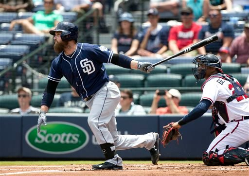 San Diego Padres' Derek Norris (3) follows through with an RBI-base hit as Atlanta Braves catcher Christian Bethancourt (27) looks on during the first inning of a baseball game, Thursday, June 11, 2015, in Atlanta.