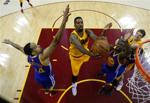 Cleveland Cavaliers guard J.R. Smith (5) shoots between Golden State Warriors guard Shaun Livingston (34), left, and forward Harrison Barnes (40) during the second half of Game 4 of basketball's NBA Finals in Cleveland, Thursday, June 11, 2015. The Warrio