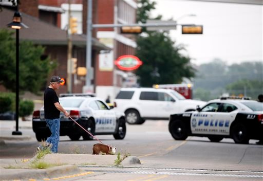 A resident walks his dog past police blocking the road near Dallas Police headquarters, Saturday, June 13, 2015, in Dallas. Police Chief David Brown says a police sniper has shot the suspect in an overnight attack on police headquarters and that the depar
