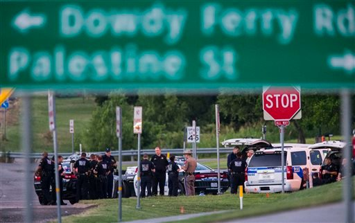 Police officers gather at the intersection of Interstate 45 and E Palestine Street, where police have cornered a suspect in a van on Saturday, June 13, 2015 in Hutchins, Texas. Police Chief David Brown says a police sniper has shot the suspect in an overn