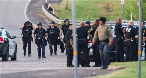 Dallas SWAT and other police officers gather at the intersection of Interstate 45 and E Palestine Street, where police have cornered a suspect in a van on Saturday, June 13, 2015 in Hutchins, Texas. Police Chief David Brown says a police sniper has shot t