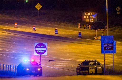 Interstate 20 is closed at E Palestine Street, where police have cornered a suspect in a van on Saturday, June 13, 2015 in Hutchins, Texas. Police Chief David Brown says a police sniper has shot the suspect in an overnight attack on police headquarters an