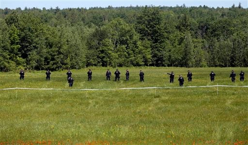 Law enforcement officers walk in a field along Route 3 on Saturday, June 13, 2015, in Saranac, N.Y. Hundreds of law enforcement personnel have begun an eighth day searching for David Sweat and Richard Matt, two killers who used power tools to cut their wa