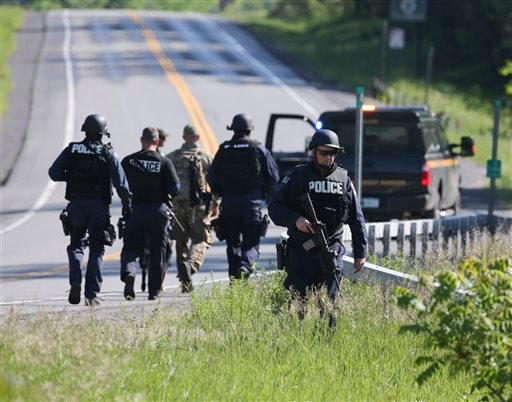 Law enforcement officers search along Route 3 on Saturday, June 13, 2015, in Saranac, N.Y. Hundreds of law enforcement personnel have begun an eighth day searching for David Sweat and Richard Matt, two killers who used power tools to cut their way out of