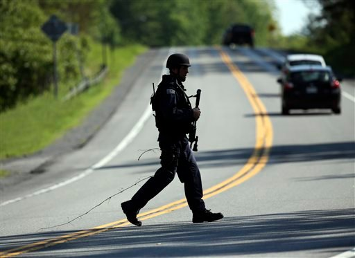 A law enforcement officer walks across Route 3 on Saturday, June 13, 2015, in Saranac, N.Y. Hundreds of law enforcement personnel have begun an eighth day searching for David Sweat and Richard Matt, two killers who used power tools to cut their way out of