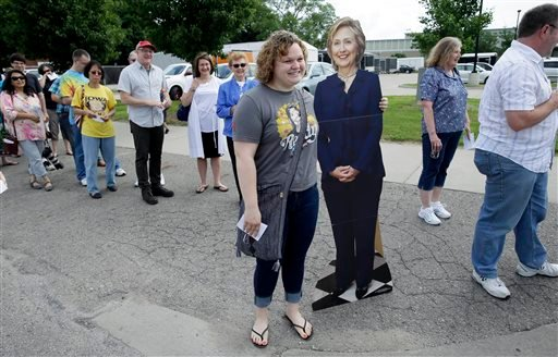 Caitlin Wilson, of Altoona, Iowa, poses with a cardboard cutout of Democratic presidential candidate Hillary Rodham Clinton outside a rally, Sunday, June 14, 2015, in Des Moines, Iowa. Seeking an army of volunteers, Clinton is trying to build an organizat