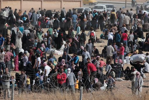 In this photo taken from the Turkish side of the border between Turkey and Syria, in Akcakale, Sanliurfa province, southeastern Turkey, Syrian refugees wait on the Syrian side of the border in order to cross, Saturday, June 13, 2015. Turkey's emergency ma