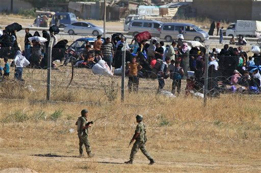 In this photo taken from the Turkish side of the border between Turkey and Syria, in Akcakale, Sanliurfa province, southeastern Turkey, Turkish soldiers, bottom, walk as Syrian refugees wait on the Syrian side of the border in order to cross, Saturday, Ju