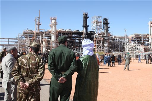 In this Jan. 31, 2013 file photo, Algerian soldiers and officials stand in front of the gas plant in Ain Amenas, seen in background, during a visit organized by the Algerian authorities for news media. The U.S. said the military launched an airstrike Satu