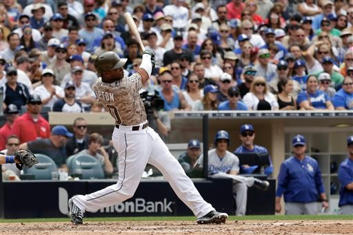San Diego Padres' Justin Upton hits a two-RBI single while batting against the Los Angeles Dodgers during the fifth inning of a baseball game, Sunday, June 14, 2015, in San Diego. (AP Photo/Gregory Bull)