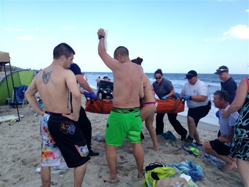 Emergency responders assist a teenage girl at the scene of a shark attack in Oak Island, N.C., Sunday, June 14, 2015. Mayor Betty Wallace of Oak Island, a seaside town bordered to the south by the Atlantic Ocean, said that hours after the teenage girl suf