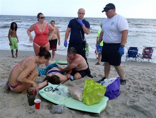 People assist a teenage girl at the scene of a shark attack in Oak Island, N.C., Sunday, June 14, 2015. Mayor Betty Wallace of Oak Island, a seaside town bordered to the south by the Atlantic Ocean, said that hours after the teenage girl suffered severe i