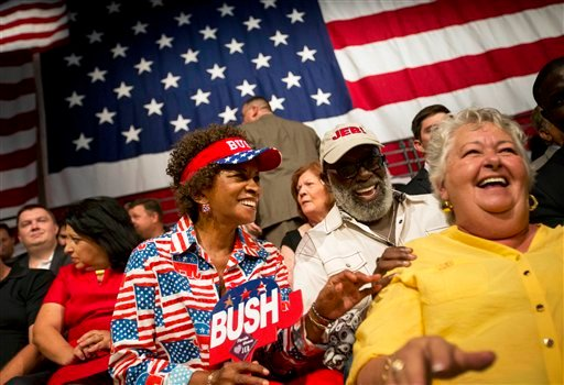 From left, Wilhelmina Austin, T. Willard Fair, both of Miami and Cynthia Handley, of Cocoa Beach, Fla., laugh while sitting in their seats at Miami Dade College in Miami, Monday, June 15, 2015, before former Florida Gov. Jeb Bush is expected to formally j