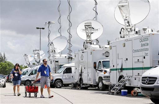 Members of the media pass a row of television live trucks as they arrive at Miami Dade College's Theodore Gibson Health Center, before an announcement by former Florida Gov. Jeb Bush at the facility, Monday, June 15, 2015, in Miami. Bush is expected to an