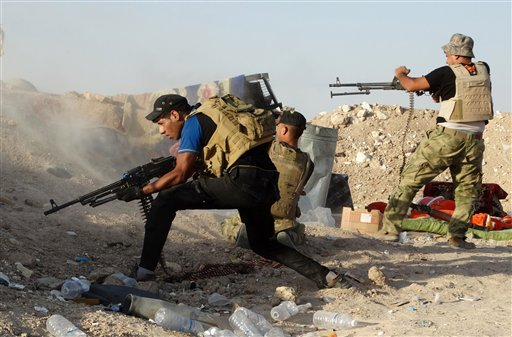 In this photo taken Monday, June 15, 2015, Iraqi security forces defend their positions against Islamic State group attack in Husaybah, 8 kilometers (5 miles) east of Ramadi, Iraq. The Islamic State group still holds about a third of Iraq and Syria, inclu