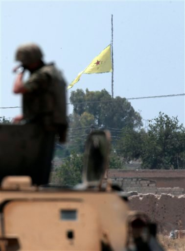 In this photo taken from the Turkish side of the border between Turkey and Syria, in Akcakale, southeastern Turkey, a Turkish soldier stands on an armoured personnel carrier as in the background a flag of the Kurdish People's Protection Units, or YPG, is