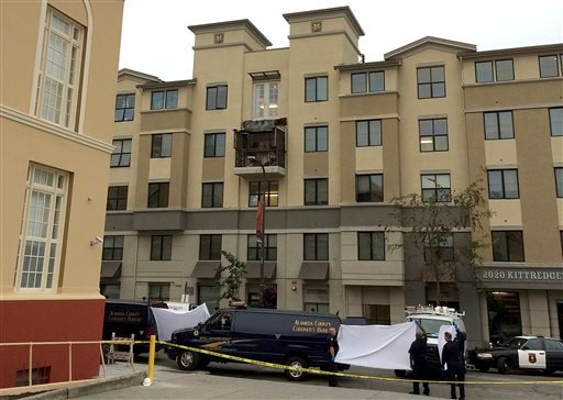 Police and officials stand outside of the Library Gardens apartment complex, where a fourth floor balcony rests on the balcony below after collapsing in Berkeley, Calif., Tuesday, June 16, 2015.