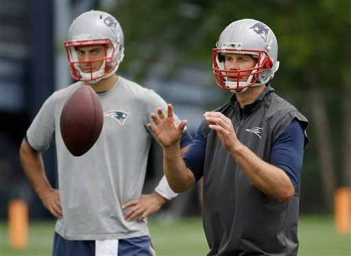 New England Patriots quarterback Tom Brady takes a snap as backup quarterback Jimmy Garoppolo looks on during an NFL football minicamp, Wednesday, June 17, 2015, in Foxborough, Mass.