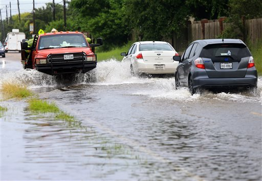 Vehicles drive in flooded waters caused by a heavy rains Wednesday, June 17, 2015, on Glenoak Drive in Corpus Christi, Texas. (Gabe Hernandez/Corpus Christi Caller-Times via AP)