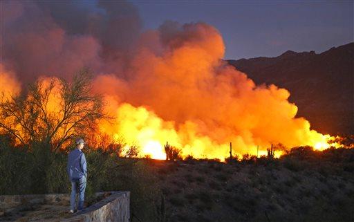 Justin Winsor watches a wildfire from the Breezeway Trailer Park Wednesday, June 17, 2015 in Kearny, Ariz. (David Kadlubowski/The Arizona Republic via AP)