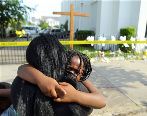 Kearston Farr hugs her 5-year-old daughter Taliyah visiting a memorial in front of the Emanuel AME Church on Friday, June 19, 2015 in Charleston, S.C. Dylann Storm Roof, 21, is accused of killing nine people during a Wednesday night Bible study at the chu