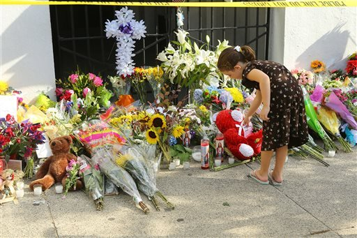 Adeline Daby, 6, places a note in front of the Emanuel AME Church on Friday, June 19, 2015 in Charleston, S.C. Dylann Storm Roof, 21, is accused of killing nine people during a Wednesday night Bible study at the church. ( Curtis Compton/Atlanta Journal-Co