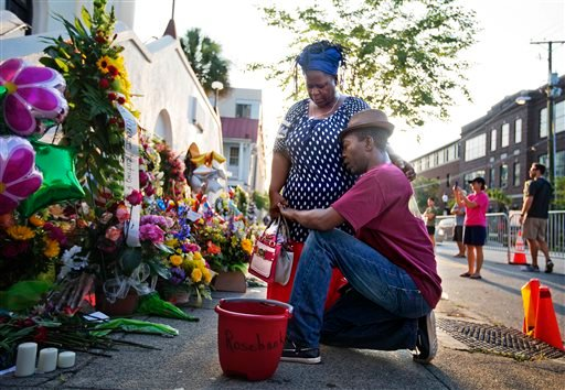 """Allen Sanders, right, kneels next to his wife Georgette, both of McClellanville, S.C., as they pray at a sidewalk memorial in memory of the shooting victims in front of Emanuel AME Church Saturday, June 20, 2015, in Charleston, S.C. """"You can't have love a"""