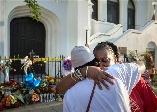 Mourners Cynthia Wright-Murphy, right, hugs her sister Carolyn Wright-Porcher, right, outside the Emanuel AME Church, Saturday, June 20, 2015 in Charleston, S.C. A steady stream of people brought flowers and notes and shared somber thoughts at a growing m