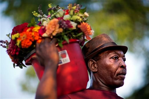 """Allen Sanders, of McClellanville, S.C., brings a bucket of flowers to place at a sidewalk memorial in memory of the shooting victims in front of Emanuel AME Church Saturday, June 20, 2015, in Charleston, S.C. """"We're just going to have to love one another,"""