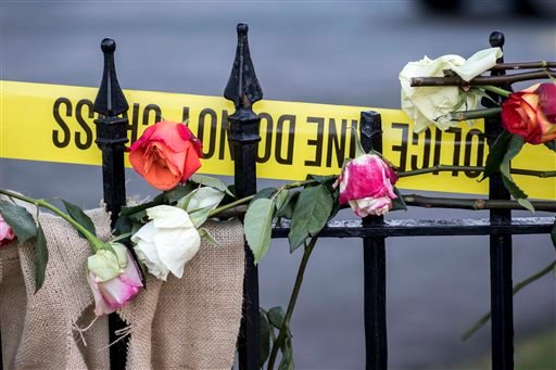 Roses and crime scene tape are laced through the wrought iron fence at the memorial on the sidewalk in front of the Emanuel AME Church, Saturday, June 20, 2015 in Charleston, S.C. People started visiting the site well before sunrise four days after a gunm
