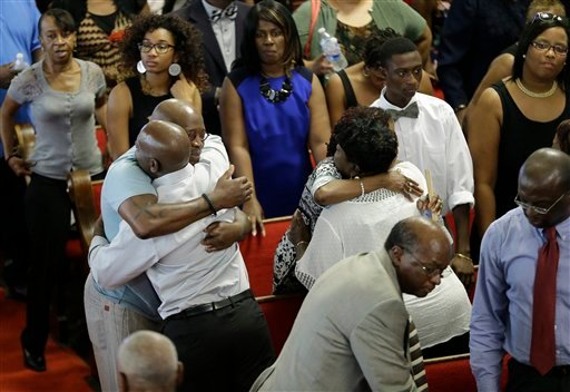 Parishioners embrace at the Emanuel A.M.E. Church Sunday, June 21, 2015, in Charleston, S.C., four days after a mass shooting that claimed the lives of it's pastor and eight others. (AP Photo/David Goldman, Pool)
