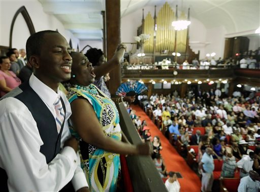 Parishioners Shakur Francis, left, and Karen Watson-Fleming sing at the Emanuel A.M.E. Church Sunday, June 21, 2015, in Charleston, S.C., four days after a mass shooting that claimed the lives of it's pastor and eight others. (AP Photo/David Goldman, Pool