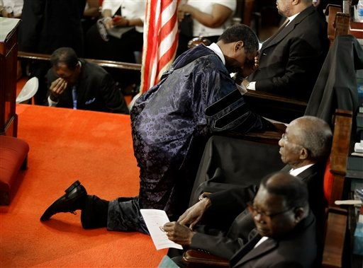 The Rev. Norvel Goff, right, prays at the empty seat of the Rev. Clementa Pinckney at the Emanuel A.M.E. Church four days after a mass shooting that claimed the lives of Pinckney and eight others on Sunday, June 21, 2015, in Charleston, S.C. (AP Photo/Dav