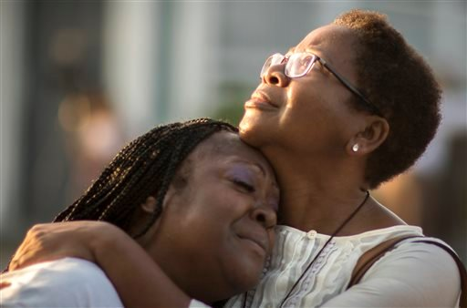Gillettie Bennett, right, comforts Clarissa Jackson, left, Sunday, June 21, 2015, while she waits in line for Emanuel AME Church's first worship service since nine people were fatally shot at the church during a Bible study group, in Charleston, S.C. (AP