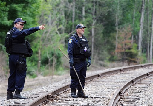 New York State Department of Corrections officers search the railroad tracks after a possible sighting of the two murder convicts who escaped from a northern New York prison two weeks ago, Sunday June 21, 2015, in Friendship, N.Y. State police said a woma