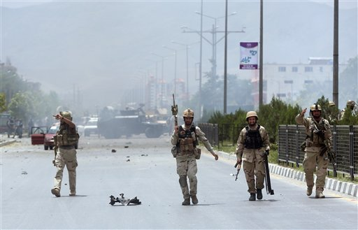 Afghan security forces inspect the site of a suicide attack during clashes with Taliban fighters in front of the Parliament, in Kabul, Afghanistan, Monday, June 22, 2015. The Taliban launched a complex attack on the Afghan parliament Monday, with a suicid