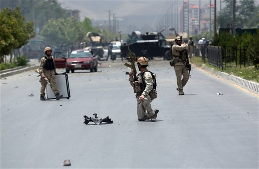 Afghan security forces take position at the site of a suicide attack during clashes with Taliban fighters in front of the Parliament, in Kabul, Afghanistan, Monday, June 22, 2015. The Taliban launched a complex attack on the Afghan parliament Monday, with