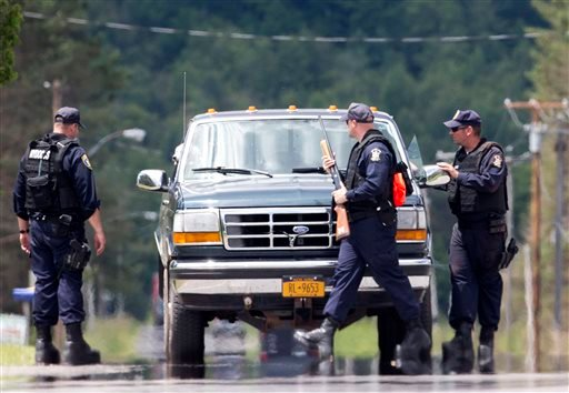 Corrections officers stop a vehicle as the search for two escaped prisoners from Clinton Correctional Facility in Dannemora continues Monday, June 22, 2015, in Owls Head, N.Y. Searchers on Monday swarmed the heavily wooded area about 20 miles west of the