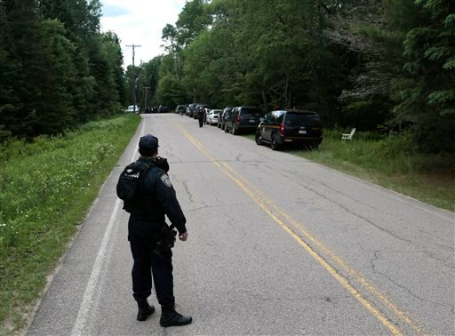 A corrections officer stands on a road as the search continues for two escaped prisoners from the Clinton Correctional Facility in Dannemora, on Monday, June 22, 2015, in Owls Head, N.Y. In the more than two weeks since inmates David Sweat and Richard Mat