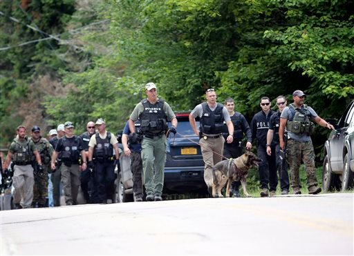 Law enforcement officers walk along a road as the search continues for two escaped prisoners from the Clinton Correctional Facility in Dannemora, on Monday, June 22, 2015, in Owls Head, N.Y. In the more than two weeks since inmates David Sweat and Richard