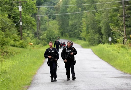 Law enforcement officers walk along a road while searching for two prison escapees from Clinton Correctional Facility in Dannemora, on Tuesday, June 23, 2015, in Owls Head, N.Y. (AP Photo/Mike Groll)