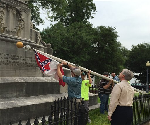 State workers take down a Confederate national flag on the grounds of the state Capitol, June 24, 2015, in Montgomery, Ala. Alabama Gov. Robert Bentley ordered Confederate flags taken down from a monument at the state Capitol.(AP Photo/Martin Swant)