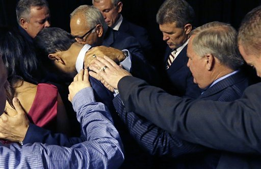 Louisiana Gov. Bobby Jindal, center, prays backstage with a group of local pastors before he announces his candidacy for president in Kenner, La., Wednesday, June 24, 2015. (AP Photo/Gerald Herbert)